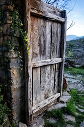 old wooden door partially opened from a village house with small yellow flowers on one side and a view of the countryside in the background