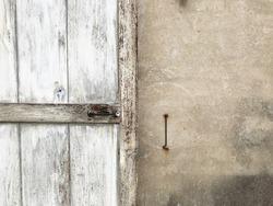 old wooden  door ,rusty hand bar ,and rusty door hook on the  dirty concrete wall
