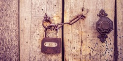 Old wooden door with a handle, chain and lock. Boho style
