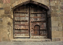 Old wooden door with some small door in daulatabad fort , Maharastra State in India.Daulatabad fort built in 14th century located near Aurangabad. Ancient wooden door on around arch with stone wall