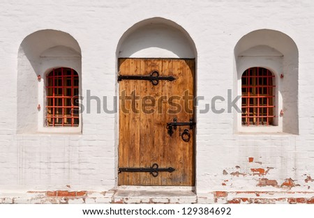 old wooden door with white wall