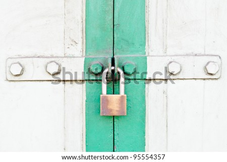 Old wooden doors are locked with a padlock.