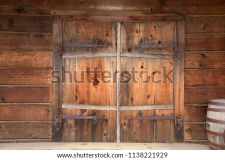 Old wooden double doors with rusty weathered hardware, wooden barrels stacked beside door. Close up.
