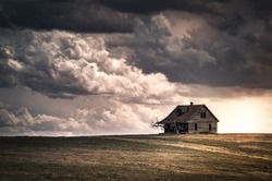 Old wooden farmhouse in the countryside at sunset with storm  clouds in the sky. There is a short grass meadow around the house.