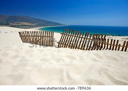 Old wooden fence on deserted white sandy beach dunes on a hot sunny day in Tarifa Spain