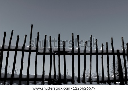Old Wooden Fence Over Sky Background. Winter Background. Wooden Background. Snow On The Fence. Black And White Pic.