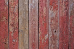 Old wooden fence painted in red, peeling cracked paint. Texture of red wooden planks, old barn wall, rustic style