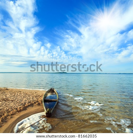 Old wooden fishing boat flooding near the lake shore and summer sky with sun behind (Svityaz, Ukraine)