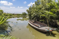Old wooden fishing boat on the river green plant beside, Thai traditional Thai style house background far away  in sunny day and blue sky.