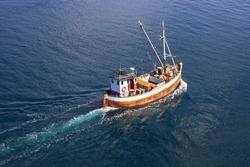 Old wooden fishing boat trawler on sea.