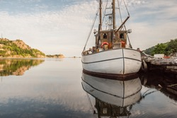 Old wooden fishingboat docked. Calm water..