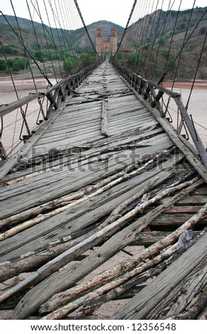 Old wooden foot bridge over the river, with two towers on other side. Bolivia