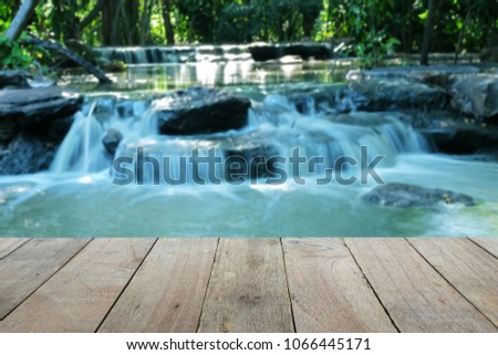 Old wooden foreground with blurred Waterfall background, Old wooden foreground with blurred Waterfall background, empty space Place a product. Nature and health concept #1066445171