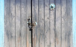 Old wooden gate closed with a padlock on a chain. Retro wood door with vintage metal decorative elements