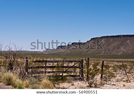 Old wooden gate in desert with mountains in background. Clear blue sky.