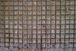 Old wooden gate studded with slats. Fragment. Old paint cracked. Can be used as background or texture. Close-up