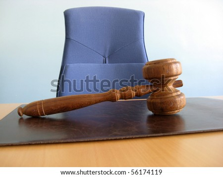 Old wooden gavel ,blue chair and court desk