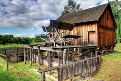 old wooden historic water mill standing on a small stream