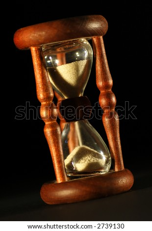 Old wooden hour glass on black - stock photo