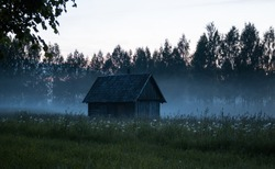Old wooden house in the evening mist.