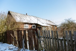 Old wooden house in village. Non-residential collapsing building. Poverty. Rotten fence. Homeland memories. Parental home. Auction for the sale of a land plot with dilapidated building for demolition.
