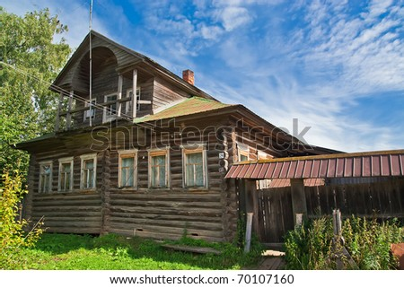 old wooden house on the background of blue sky with white clouds