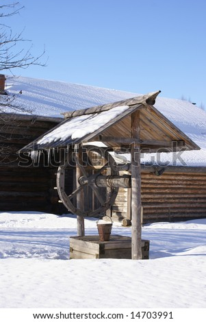 Old wooden house with draw-well in front. winter