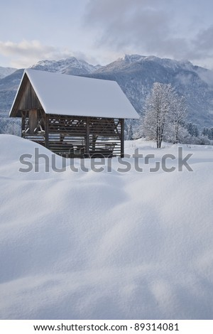 old wooden hut covered with fresh snow in winter, bohinj region, slovenia