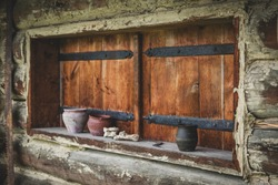 Old wooden hut in the rural Sub-carpathian mountain area. Old  historic early medieval house with ceramic pot and cups on a windowsill. Wooden closed shutters. Slavic hut built of wood, straw and clay