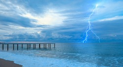 Old wooden jetty during stormy clouds on the Mediterranean sea with Thunderbolt strike