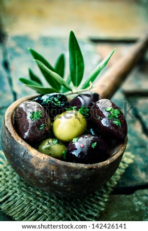 Old wooden ladle or large spoon filled with seasoned black and green olives decorated with an olive-tree branch