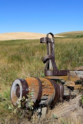 old wooden lichen covered spoke less wagon wheel weathered and rusted  on a grass and agricultural landscape
