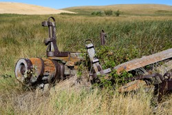 old wooden lichen covered spoke less wagon wheel weathered and rusted  on a grass and agricultural prairie landscape
