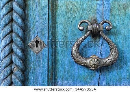 Old wooden light blue door  with aged metal door handle. Architectural textured background