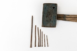 Old wooden mallet and rusty nails on a white background