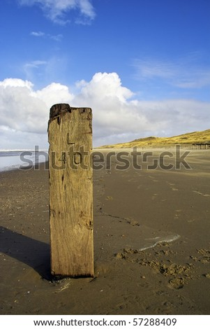Old wooden marker pole on a beach in Holland