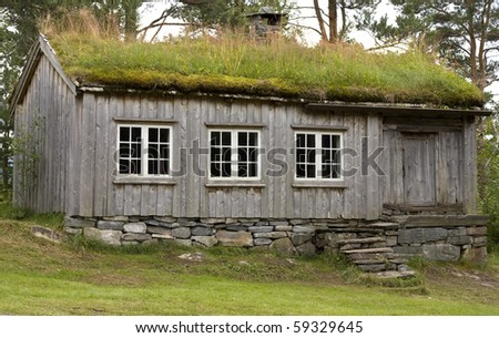 Old wooden mountain cabin with turf roof