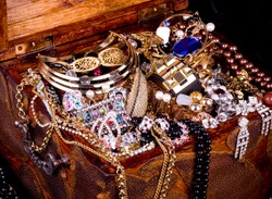 Old wooden open chest with golden jewelry