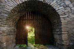Old wooden open door in gates to ancient castle. Archway in stone fortress wall. Dark medieval woods doorway to summer sun light secret garden