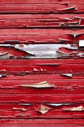 Old wooden painted red textured background with peeling paint