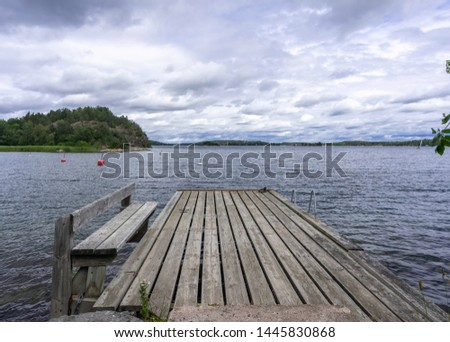 Old wooden pier. Empty berth on the Baltic sea coast. Dramatic cloudy sky. Horizon. Vintage Picture. Seascape: amazing view. Beautiful picture of sea coast line in Scandinavia. Empty jetty on storm.