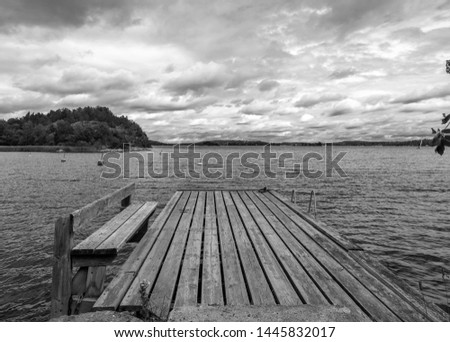Old wooden pier. Empty berth on the Baltic sea coast. Monochrome. Dramatic cloudy sky. Horizon. Vintage Picture. Seascape: amazing view. Beautiful picture of sea coast line in Scandinavia. Empty jetty