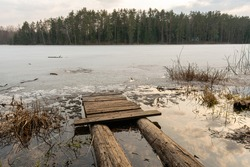 Old wooden pier on small country lake. Melted ice near the shore on the lake in the woods. Evening time in early spring
