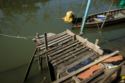 Old wooden pier that required for repairing. Dilapidated wooden pier on a dirty canal.