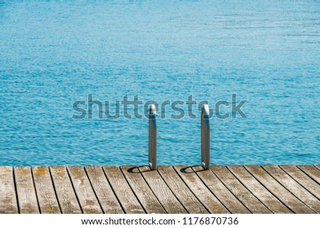 Old wooden pier with metal ladder into the sea, lake, water