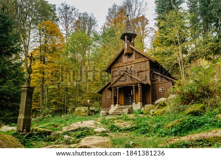 Photo of  Old wooden pilgrimage rural Chapel of Virgin Mary (CZ: Stozecka kaple) and iron cross, standing in a forest at the altitude of 950 m, Czech Republic, Sumava National Park. Folk wood carving.