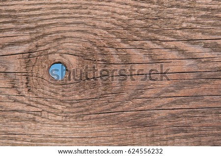 Old wooden plank with hole; Brown wooden board with round hole for background; Blue sky visible through knothole of old wooden fence