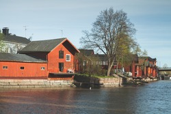 Old wooden red houses and barns are on the river coast in historical part of Porvoo town, Finland