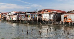 Old wooden rickety houses and footbridges on stilts. coastal view of poor living district of Kota Kinabalu, Malaysia