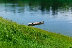 Old wooden rowing boat on the blue river water by the green riverbank